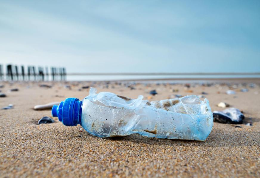A broken bottle of water lying on a beach