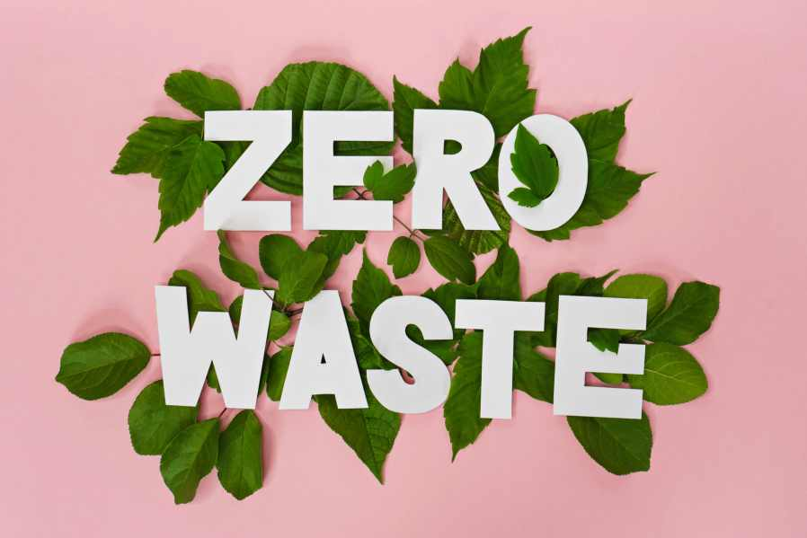 The words zero waste lying on a bunch of green leaves on a pink background