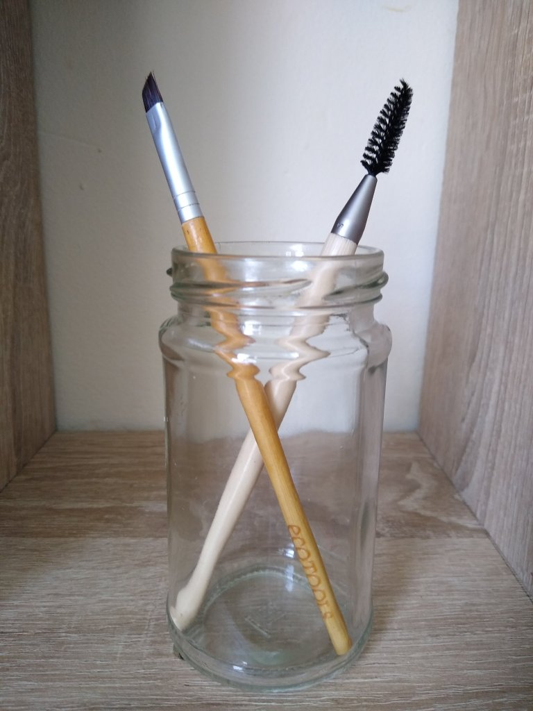 A jar containing two makeup brushes: angled brush and brow spoolie